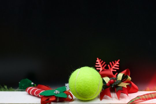 Tennis with Christmas ornament on black background.