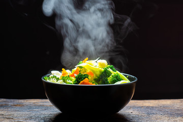 The steam from the vegetables carrot broccoli Cauliflower in a black bowl, a steaming. Boiled hot Healthy food on table on black background,hot food and healthy meal concept