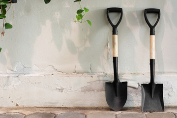 Garden tools shovel on wall background.