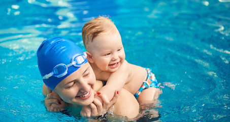 Child having fun in water with mom. Little wet boy smiling holding on his mother's back and happy woman with swimming cap and goggles. Blue turquoise water on background. Horizontal portrait view