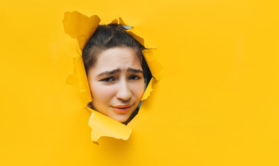 What? Funny angry teenage girl peeping through hole on yellow paper. The concept of surprise, skeptic, sad mood from what he saw. Discounts, sales, surprise. Copy space.