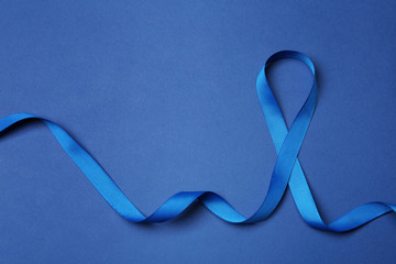 Blue ribbon on color background, top view. Colon cancer awareness concept