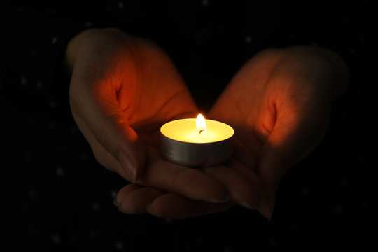 Woman holding burning candle in darkness, closeup