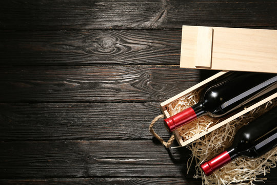 Crate and bottles of wine on wooden table, flat lay. Space for text