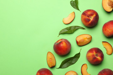 Flat lay composition with sweet juicy peaches on green background, space for text