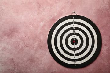 Dart board hanging on pink textured wall. Space for text