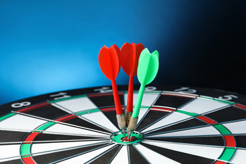 Arrows hitting target on dart board against blue background