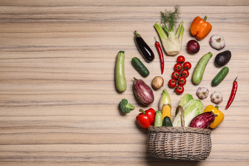 Flat lay composition with different vegetables and wicker basket on wooden background. Space for text