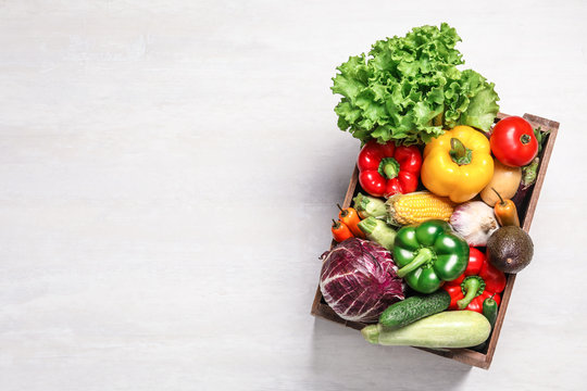 Crate with different fresh vegetables on light background, top view. Space for text