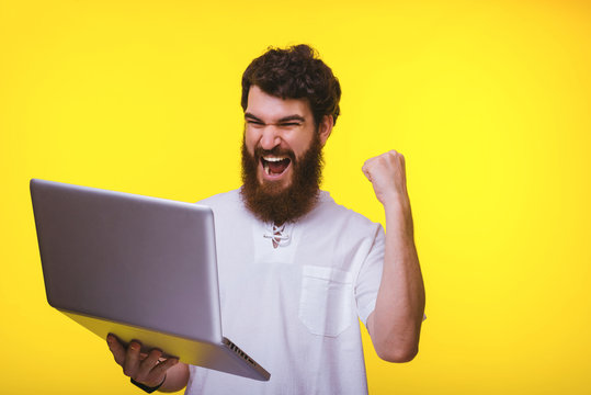 Photo of amazed young man celebrating success and looking at his laptop