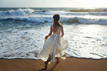 Beautiful bride running on the beach