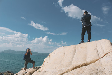 Professional photographer taking picture on the rocky beach of Phu Yen, Vietnam