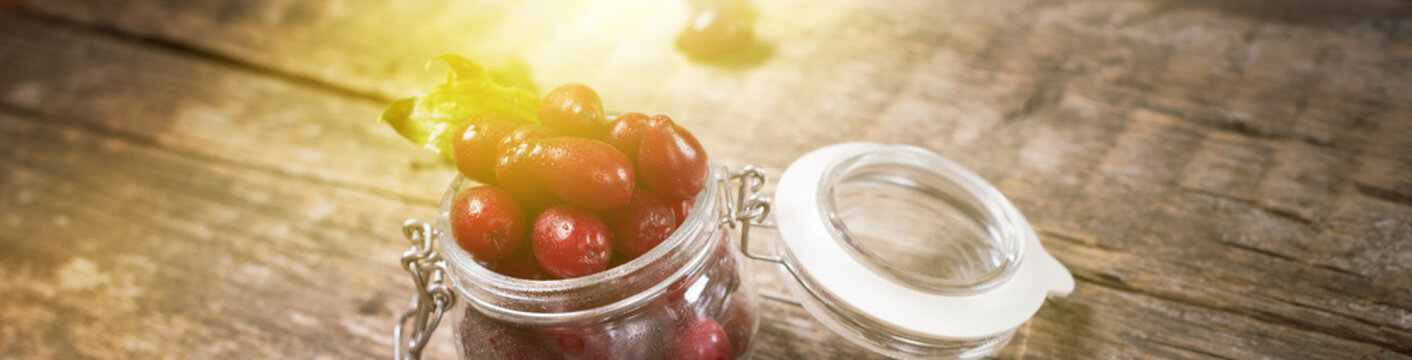 Ripe red cornel berries in small glass jar