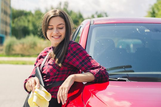 Car detailing - the female holds the microfiber in hand and polishes the car. Selective focus. Girl cleaning red car 2018
