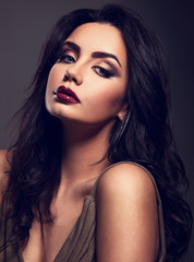 Beautiful bright makeup woman with long black curly hair style, burgundy lipstick with vamp look on grey background. Closeup
