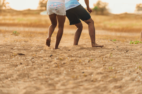 Two friends having fun together on sandy beach while playing soccer