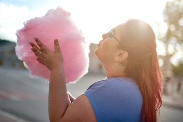 Fat young woman walking with cloud of candy-floss