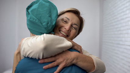 Fototapeta Happy woman hugging doctor, good test results, recovery and remission, gratitude obraz