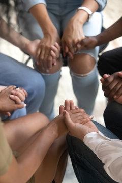 Closeup view people sitting together holding hands during therapy session