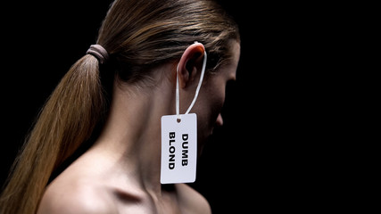 Lady with dumb blonde tag on ear against dark background, humiliation stereotype