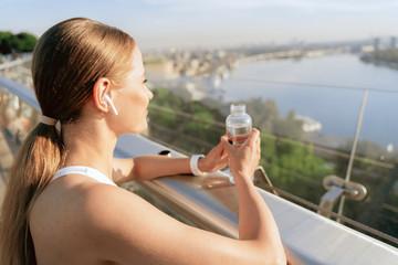 Sportive happy lady with bottle of water on bridge