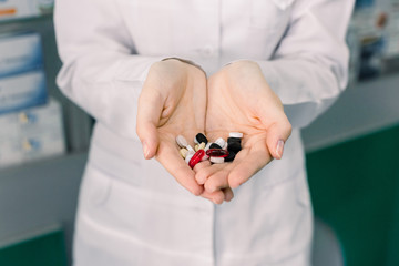 Close up picture of doctor or pharmacist hands holding colorful pills. Pharmacy, medicines concept