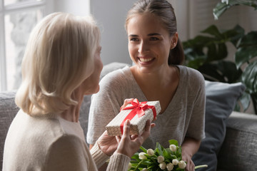 Middle aged mother receiving from grown up daughter gift box