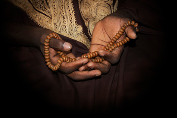 Hands of a Muslim man holding a rosary