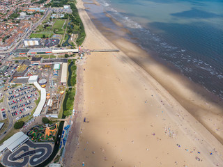Aerial photo of the British seaside town of Skegness in the East Lindsey a district of Lincolnshire, England, showing the fairground funfair rides and families having fun and relaxing on the beach. Fototapete