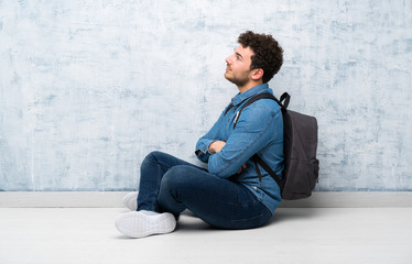 Young man sitting on the floor with backpack Wall mural