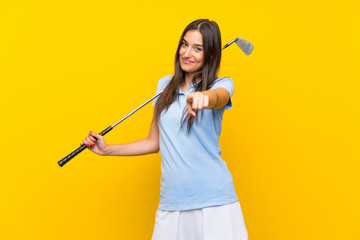 Young golfer woman over isolated yellow wall points finger at you with a confident expression