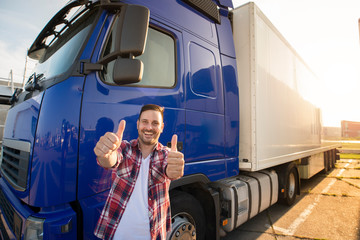 Portrait of happy smiling middle aged truck driver standing by his truck and holding thumbs up. Successful transportation service. Wall mural