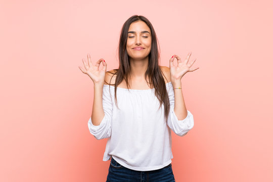 Young woman over isolated pink background in zen pose