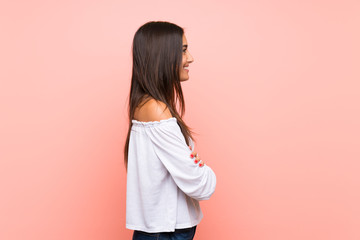 Young woman over isolated pink background in lateral position