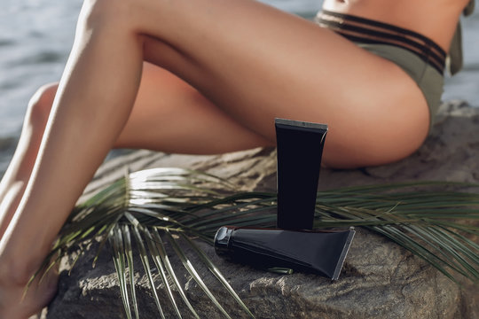 Beach woman. Close-up of tubes of cream , sunscreen. Bronzer for the body. UV protection on sexy women's bikini thigh legs close up. Copy Space