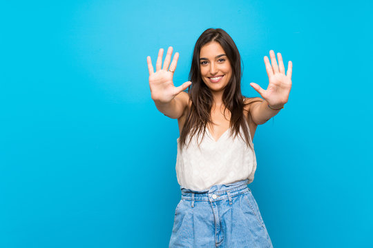 Young woman over isolated blue background counting ten with fingers
