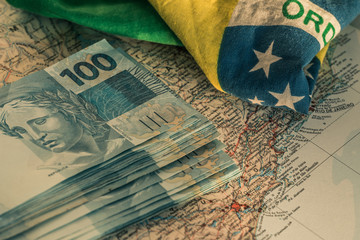 Photo sur Aluminium Brésil Brazilian money, 100 reais banknotes on the map of Brazil with a fragment of the national flag