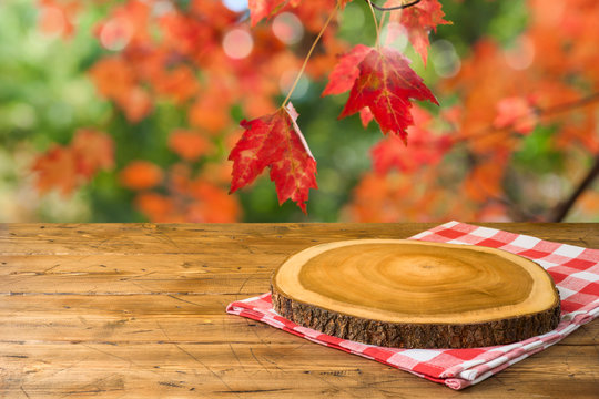 Empty wooden table with tablecloth and wooden board over autumn nature park background