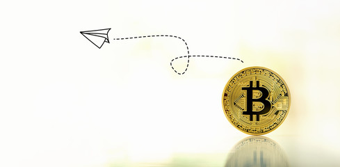 Paper airplane with gold bitcoin cryptocurrency coin