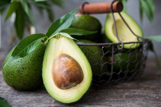 Fresh green avocado on wooden background. Selective focus. Horizontal orientation.