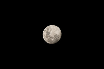Cloudless night sky with full moon and deep black universe in the background as panorama view for wallpaper and copy space