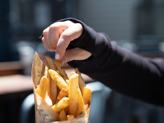 Woman in long sleeve black shirt taking crispy French fry on bright day