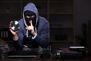 Male thief in balaclava in the office night time - fototapety na wymiar
