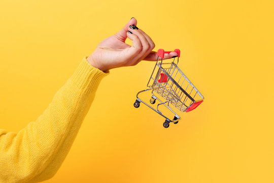 Buying things at market shops concept. Woman hand holding small tiny shopping cart trolley over trend yellow background