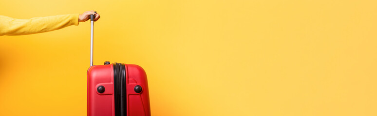 Travel red suitcase and hand over yellow background, panoramic  mock up image