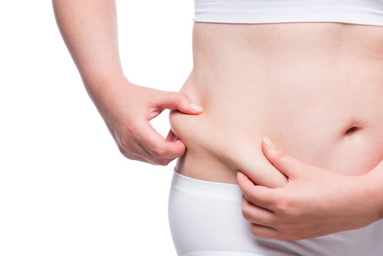 fat woman measures the layer of subcutaneous fat on the abdomen, closeup belly isolated