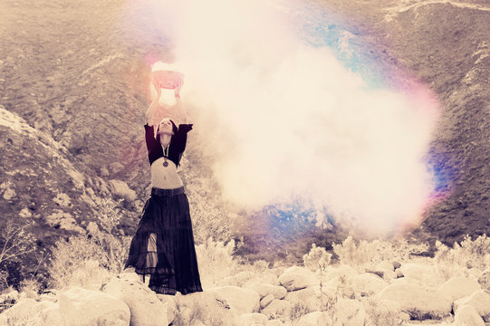 Priestess woman holding magic potion smoking above her head in the wilderness.
