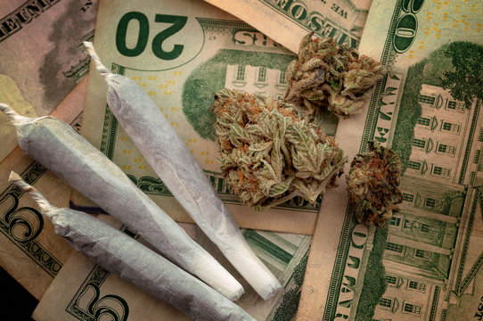 Gateway drug theory, junkie substance abuse and unhealthy narcotic drugs concept theme with close up on cannabis buds, weed filled cigarette known as joint against a twenty dollar bills background