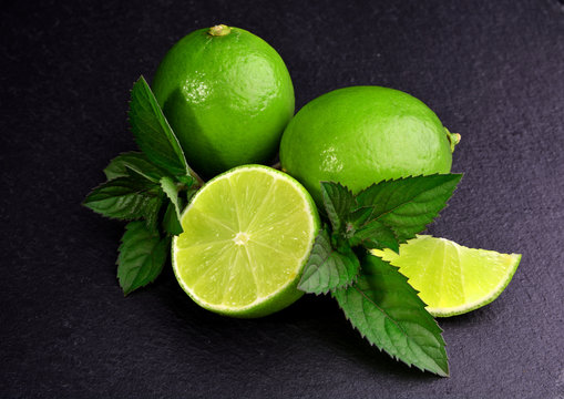 Fresh green lime and mint on black background