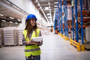 Portrait of an attractive smiling warehouse worker supervisor walking through large factory storage department looking towards shelves. Industrial worker employee controlling goods distribution. Wall mural
